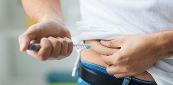 Hombre pinchándose insulina como tratamiento de la diabetes