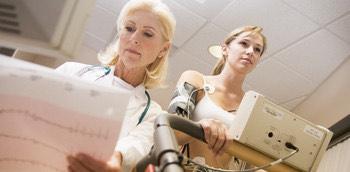 Una doctora realizando un tes de provocación de isquemia a una paciente joven