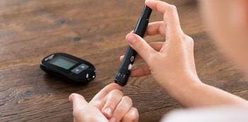 Mano de un paciente realizando un test de azúcar en sangre por diabetes