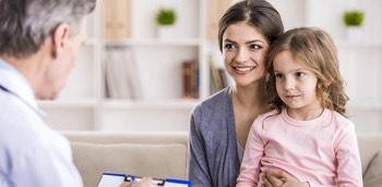 Doctor en la consulta hablando con una madre y su hija