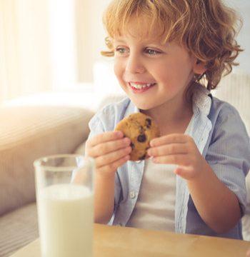 Niño desayunando un vaso de leche y una galleta
