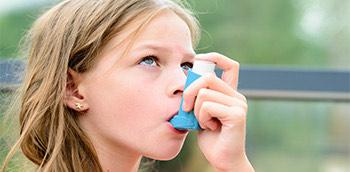 Niña con inhalador para el asma bronquial
