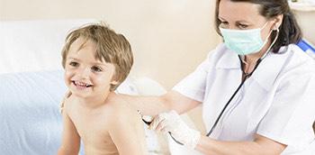 Una médico auscultando a un niño