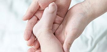 Pie de bebé entre las manos de un médico