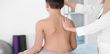 Doctor valorando la escoliosis y cifosis de un paciente