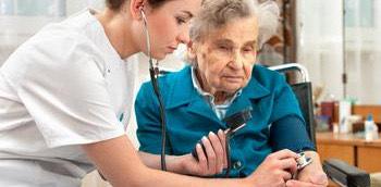 Doctora en urgencias auscultando con una paciente anciana