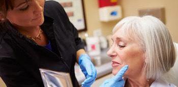 Doctora inyectando toxina botulínica a una señora en una intervención estética