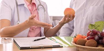 Dos médicos hablando sobre pautas nutricionales con comida delante