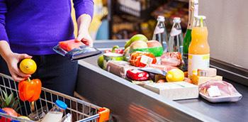 Mujer con el carro de la compra y comida en la cinta