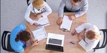 Médicos en una mesa gestionando los servicios clínicos