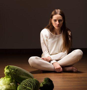 Chica con trastorno de la alimentación con comida delante
