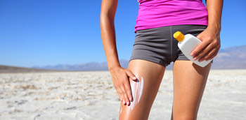Chica aplicando una crema fotoprotectora en la pierna