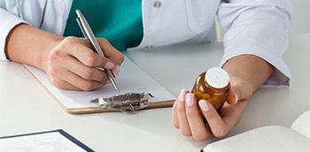 Doctor haciendo una receta con el medicamento en la mano