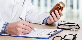 Doctor tomando notas de un medicamento en su libreta