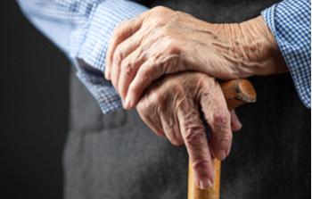 Manos de un señor mayor cogiendo un bastón de madera