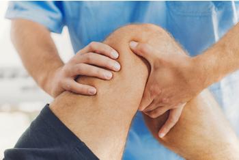Doctor ayudando a la rehabilitación de un hombre con problemas en la rodilla