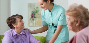 Doctora hablando con dos señoras en una residencia