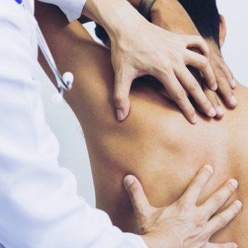 Doctor palpando la espalda de un paciente