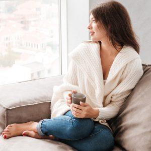 Mujer tomando café en el sofá